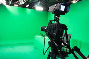 Camera facing green screen during film production