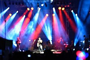 out of focus camera shot of a bunch of red and blue lights at a rock concert where the group is protected by staging & rigging insurance plans