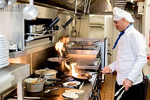 a chef cooking steaks on a gas stove that can easily break so the restaurant has purchased an equiment breakdown insurance policy