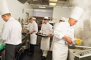 chefs cooking in the kitchen of a professional Los Angeles, CA restaurant that is covered by equipment breakdown insurance since the kitchen equipment is used every day