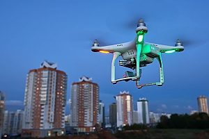 a quadcopter with green and red lights capturing a time elapse of a city while being protected with several different drone insurance policies