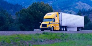 a semi truck on a highway next to a mountain range delivering food to a restaurant with commercial auto insurance to protect the supplier