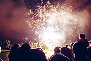 fireworks being shot off by pyrotechnicians who are covered with special event insurance since they do not want to be held liable for any injuries that may occur during the event