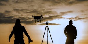 silhouettes of a film crew operating a drone that is covered with aviation liability insurance and other lines of drone insurance