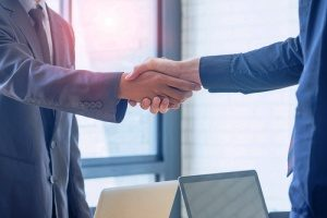 a cannabis insurance broker shaking hands with a medical marijuana dispensary owner to discuss how product liability insurance can significantly benefit the dispensary