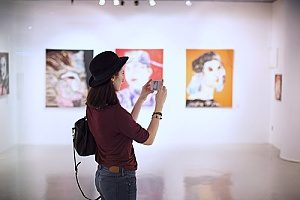 a woman taking pictures at an art exhibit that has special event insurance since there are very large sculptures