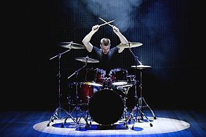 a rock drummer at a live show in front of thousands of people and therefore is covered by band insurance in case something were to happen during his performance