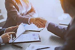 an entertainment insurance broker shaking hands with a client who is making a movie as they meet to discuss the different film production insurance options available