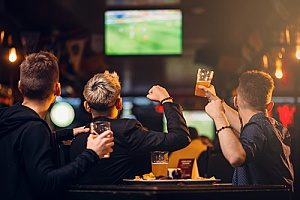 three friends watching soccer at a bar that has protections against liquor liability