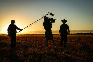 Camera crew filming in the grasslands for insured film production