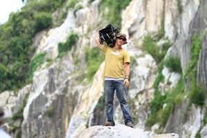 Cameraman standing on rock filming a production covered by film production insurance