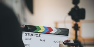 Man writing on a clapperboard for film production covered by film production insurance
