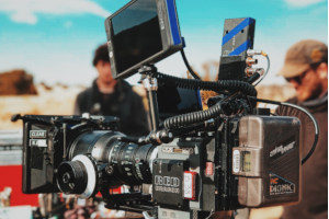 a black digital video camera mounted on a tripod on a film production set that has film production insurance
