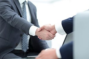 a cannabis insurance broker shaking hands with a client to discuss policies
