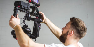 a man holding a video recorder with a stabilizer on a film production set with film production insurance