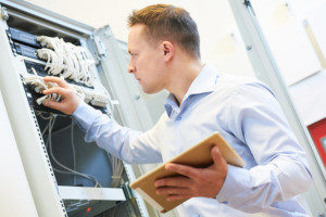 a network engineer administrator checking the server hardware that is covered by technology insurance at a data center