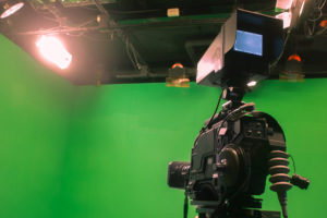 a professional camera and a green screen on the set of a short term film covered by insurance