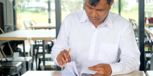 a restaurant owner looking through and signing for restaurant insurance