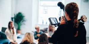 a woman holding a video camera shooting a scene for a film production with film production insurance
