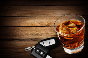 an alcholic drink next to car keys symbolizing drunk driving which can be covered by restaurant insurance