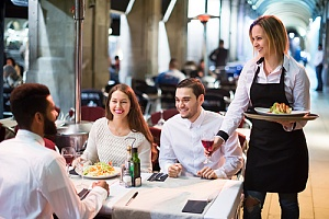 friends and server smiling at a restaurant with insurance