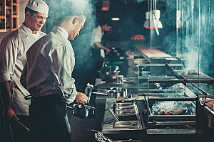 two chefs working at a busy restaurant that has workers compensation in case of an accident
