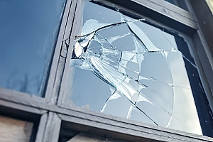 broken glass in the window of a home that is covered by insurance