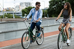 a young couple riding rental bikes in the city