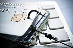 Credit card with fishing hook through it on keyboard