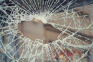 a broken window in a marijuana dispensary due to vandalism