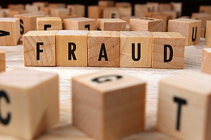 "building blocks spelling out the word ""fraud"""