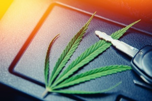 cannabis leave sitting next to keys to a automobile