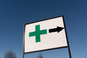 medical marijuana retailer sign with arrow pointing towards a dispensary protected with Maine cannabis insurance