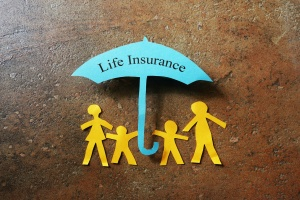 small paper cut out of family covered with life insurance