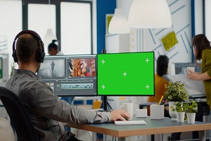 videographer using computer with chroma key mock up isolated display