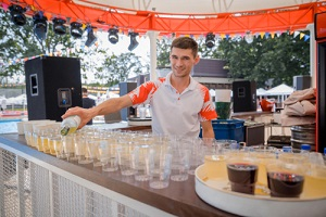 barman pouring fresh alcoholic drink into glasses