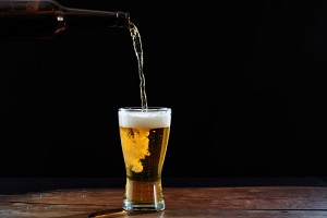 pouring beer in a glass on a wooden table