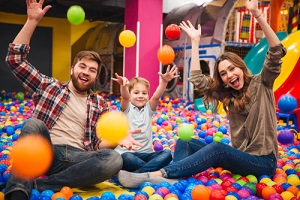 cheerful little child have fun with his parents in entertainment