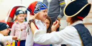 woman painting kids face on an event
