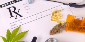 assorted cannabis products pills and cbd oil over medical prescription sheet