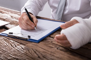 businessperson with broken arm filling health insurance claim form on wooden desk