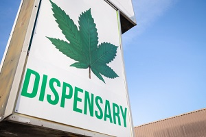 cannabis dispensary sign with a large marijuana leaf on it