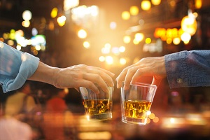 cheers clinking of friends with bourbon whisky drink in party night